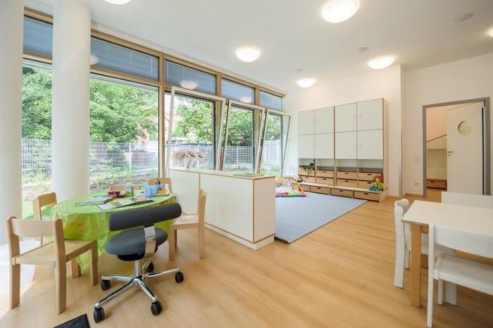 Gruppenzimmer debe.decor mit Raumteiler, Tischgruppen + Modulschrank